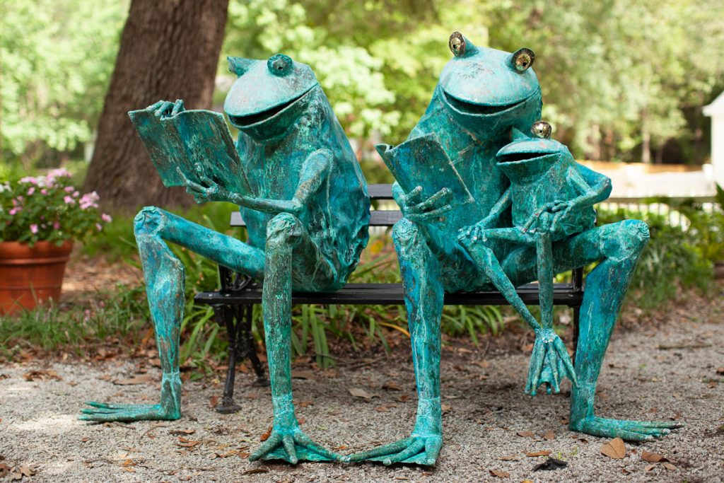 copper frog sculptures reading to child in Charleston, SC